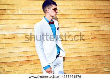 Fashion portrait of stylish man with hipster haircut, wearing trendy elegant white suit, denim shirt, bow tie and mirrored sunglasses, posing near wooden wall.  Street style look. - stock photo