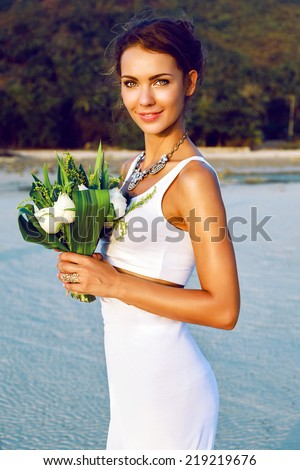Fashion portrait of tender stylish bride with simple modern wedding dress posing with amazing exotic white lotus bouquet at the beach. Evening golden sunlight. - stock photo