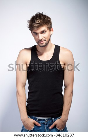 Fashion portrait of the young beautiful man in black t-shirt posing over gray background, series photo