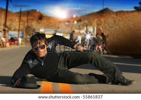Fashion portrait of trendy male model on set in street with paparazzi behind him - stock photo