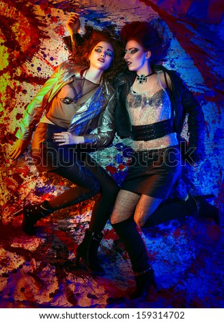 Fashion portrait of two girls in glam rock style lying on colorful background; slightly inverted