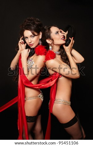 fashion portrait of two sexy brunette girls in light lingerie with long curly hair and jewelery bright makeup red lips with red ribbon isolated on black with headphones - stock photo