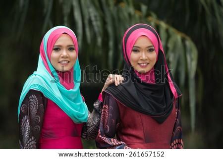 Fashion portrait of two young beautiful muslim woman wearing hijab - stock photo
