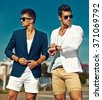 Fashion portrait of two young sexy handsome men models in casual cloth suit in sunglasses in the street behind blue sky - stock photo