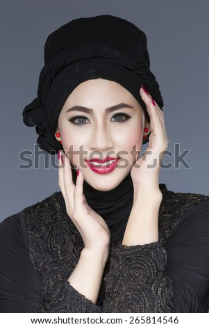 Fashion portrait of young beautiful asian muslim woman with black costume wearing hijab - stock photo