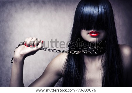 Fashion portrait of young beautiful female model. Glamour woman with long black hair and sexy hairstyle. Lady with leather collar with studs on a metal chain in hand - stock photo