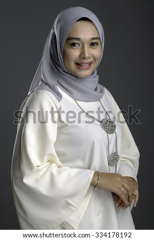 Fashion portrait of young beautiful muslim woman in modern traditional kebaya wearing hijab isolated on dark grey background - stock photo