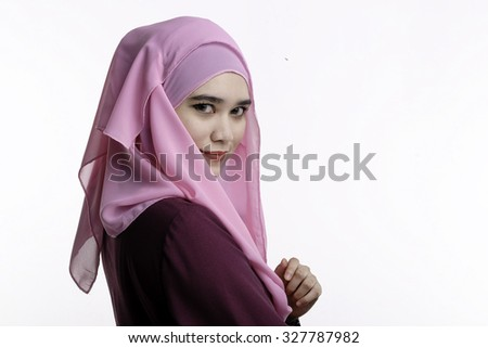 Fashion portrait of young beautiful muslim woman with maroon costume wearing pink color hijab isolated on white background - stock photo