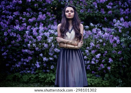 Fashion portrait of young beautiful pretty girl posing against lilac bushes in blossom - stock photo