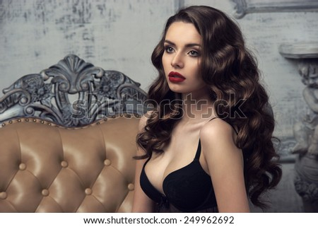 Fashion portrait of young beautiful sexy woman with long wavy hair. Pretty girl sitting in black bra or lingerie in luxury interior. - stock photo
