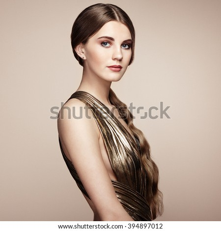 Fashion portrait of young beautiful woman in gold dress. Brunette glamour lady with perfect make up and hairstyle - stock photo