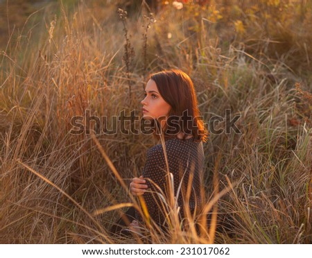 Fashion portrait of young beautiful woman, sitting in the high autumnal grass in sunset light. - stock photo