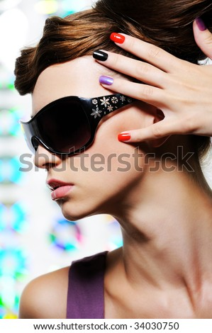 fashion portrait of young beautiful woman with hand with multicolored manicure