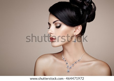Fashion portrait of young beautiful woman with jewelry. Brunette girl. Perfect make-up.  Beauty style woman with diamond accessories
