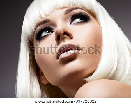 Fashion portrait of young beautiful woman with white hairs and black makeup of eye - stock photo