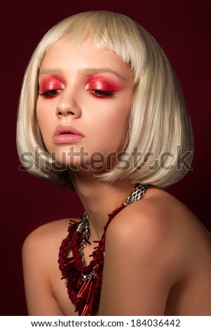 Fashion portrait of young blonde girl over wine red background - stock photo