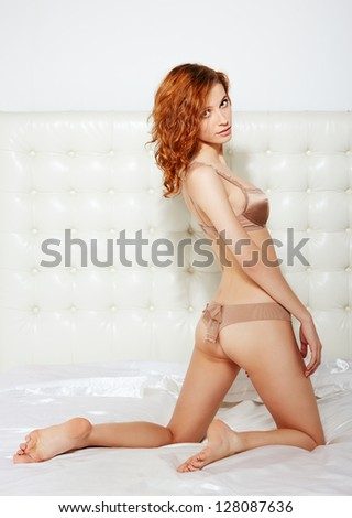 Fashion portrait of young elegant red haired woman in bed - stock photo