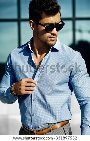 Fashion portrait of young handsome businessman model man in casual cloth  in sunglasses in the street - stock photo