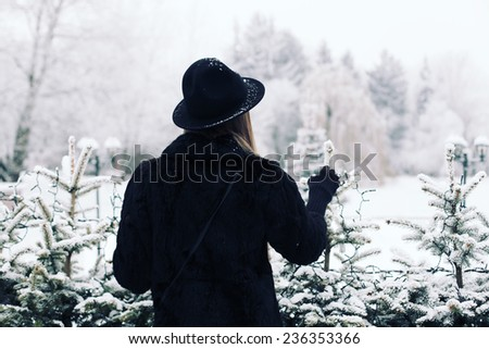 Fashion portrait of young hipster beautiful woman posing in black hat. Outdoors, lifestyle, winter. - stock photo