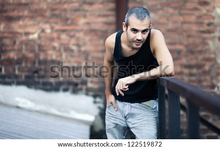 Fashion portrait of young man, behind him old  brick wall - stock photo