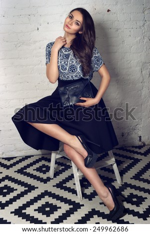 Fashion portrait of young pretty stylish girl in black skirt and blue blouse sitting at small staircase and holding black leather handbag                                - stock photo