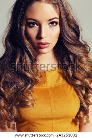 Fashion portrait of young pretty woman with blond curly lush hair and beautiful bright makeup wearing yellow dress, the wing blows her hair - stock photo