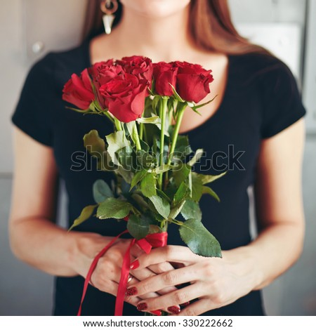 Fashion Portrait of Young Sensual Brunette Holding Bouquet of Red Roses. Selective Focus on Flowers.