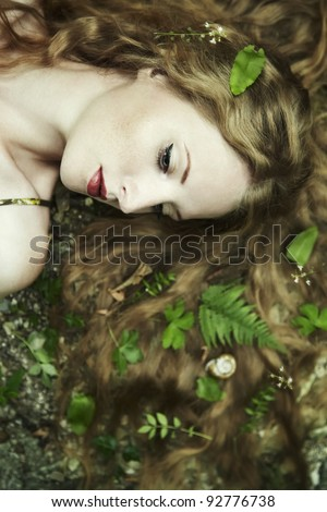 Fashion portrait of young sensual woman in garden - stock photo