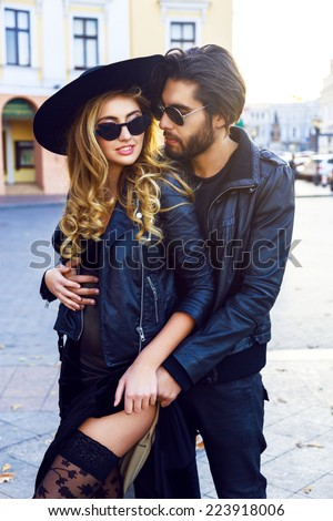 Fashion portrait of young sexy beautiful couple posing and hugs on the street, wearing trendy leather jackets, and vintage sunglasses. Outdoor fall trendy portrait of two lovers. - stock photo