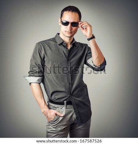 Fashion portrait of young sexy man wearing shirt and sunglasses poses on gray background - stock photo