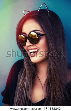 Fashion portrait of young sexy smiling brunette wearing cat ears glamour hoop at blue background. Bright instagram colors.