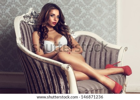 fashion portrait of young sexy woman in white lingerie sitting in old luxury armchair            - stock photo