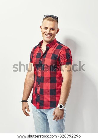 Fashion portrait of young smiling man in plaid shirt   - stock photo