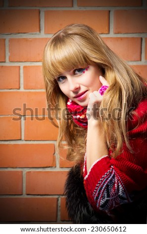Fashion portrait of young woman on red brick wall background