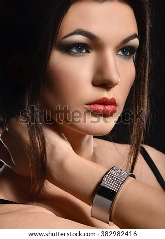 Fashion portrait of young woman. Studio shot in dark lights.
