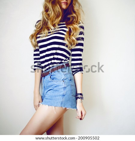 Fashion portrait of young woman with curler blonde hairs, posing near white wall in retro jeans shorts and black and white stripe t-short. - stock photo