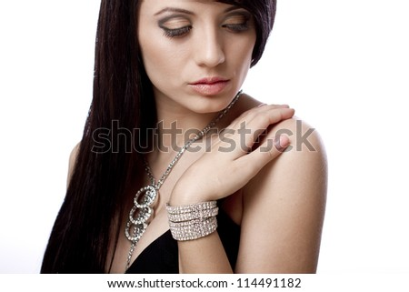Fashion portrait of young woman with dark hair and jewelry - stock photo