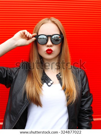 Fashion portrait pretty blonde woman with red lipstick wearing a rock black style and sunglasses having fun in city - stock photo