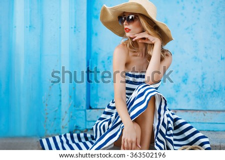 Fashion portrait. Smiling blonde woman in fashionable look. Sea style. On blue background. Style and hot girl outdoor. Woman in sun glasses and straw hat. Fashion. - stock photo