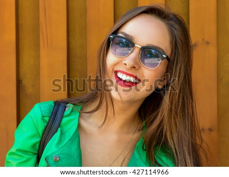 Fashion portrait stylish pretty woman in sunglasses posing in the city. Street fashion Beautiful Young Woman Outdoors. - stock photo
