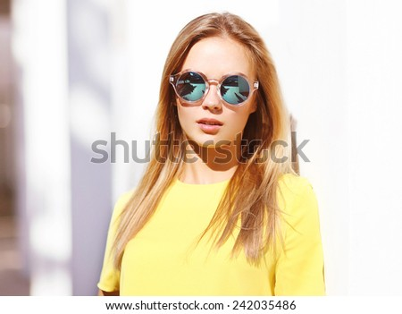 Fashion portrait stylish pretty woman in sunglasses posing outdoors in the city, street fashion - stock photo