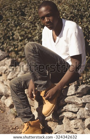 Fashion portrait stylish young african man outdoors in summer day - stock photo