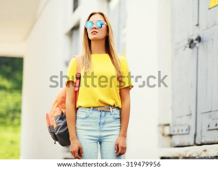 Fashion portrait trendy young woman wearing a sunglasses and t-shirt with backpack in the city - stock photo