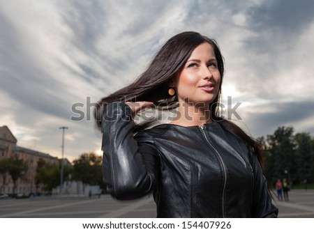 Fashion posing outdoor - russian brunette 20s years old posing outdoors weared black leather jacket head and shoulders shot against night cityscape evening street view - stock photo