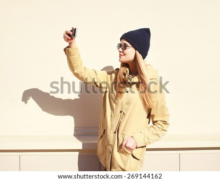Fashion pretty blonde makes selfie-portrait on the smartphone, carefree hipster girl wearing a black sunglasses and hat, enjoying and having fun outside in sunny day against the urban wall - stock photo