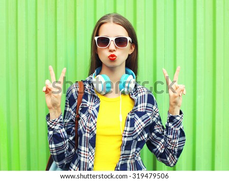 Fashion pretty cool girl wearing a sunglasses and headphones having fun over green background - stock photo