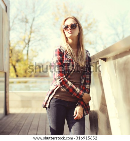 Fashion pretty woman wearing a sunglasses and checkered shirt in the city - stock photo