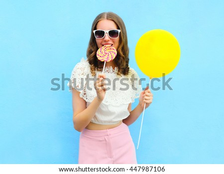 Fashion pretty woman with air balloon and lollipop over colorful blue background - stock photo