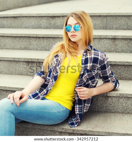 Fashion pretty young girl wearing a checkered shirt and sunglasses sitting in city - stock photo