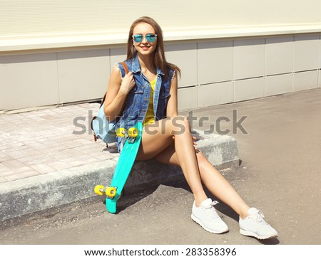 Fashion pretty young girl with skateboard and backpack outdoors in the city - stock photo